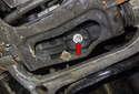 Working on the left side subframe, remove the 13mm lower motor mount fastener (red arrow).
