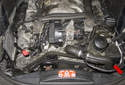 The power steering pump on W211 models with a 6-cylinder engine is mounted to the lower left side of the engine (red arrow).
