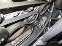 Locate the accessory drive belt tensioner (red arrow) on the left side of the engine.
