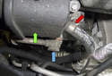 Working at the left corner of the engine, below the power steering reservoir (green arrow), using a 22 mm wrench, remove the PS pump high-pressure line (blue arrow).
