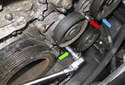 Using a ratchet with a long handle and a 17mm socket, rotate the drive belt tensioner counterclockwise to release tension and allow access to the lower power steering pump (blue arrow) E12 fastener (red arrow).