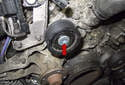 Using a T50 Torx socket, remove the idler pulley fastener (red arrow).