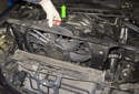Pull cooling fan up (green arrow) and remove from engine compartment