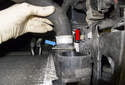 Pull radiator hose straight off radiator in direction of red arrow to remove.