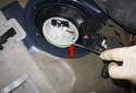Gently lever the top of the fuel filter module up to free it from the tank seal (red arrow).