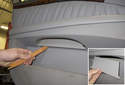 Working at the center of the door panel below the pull handle, remove the small plastic cover.