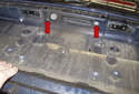 Working at the center of the trunk, remove the two T30 Torx handle fasteners (red arrows).
