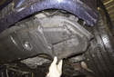 Pull the lower radiator splash shield down away from the bumper and remove it.