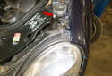 Headlight assembly: Working at the top of the headlight assembly, remove the 8mm fastener (red arrow).