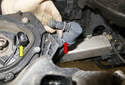 Headlight assembly: Working at the bottom of the headlight (yellow arrow), press the tab and slide the headlight washer (red arrow) out of the mounting bracket.