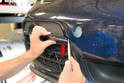 Begin by using a trim removal tool and prying out the plastic trim piece that surrounds the fog light.