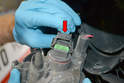 To replace the fog light bulb, squeeze down on the tab at the rear of the wiring connection (red arrow) and slide the connection backwards.
