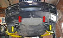 Start by removing the fasteners that connect the lower bumper cover from the under trays (red arrow).
