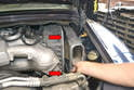 Begin by releasing the two clips for the air box lid (red arrows) and remove the lid and filter, note that on standard transmission lids there will be an additional hose you need to remove.