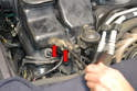 Use a 10mm socket or wrench and remove the two bolts holding the actuator bracket to the air duct (red arrows).