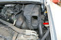If your car has a manual transmission there is a rubber hose connected to the cover by the air opening (red arrow).
