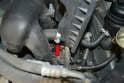 Use your long handle Philips screwdriver and loosen the hose clamp on the lower hose to airbox and slip the hose off the box (red arrow).