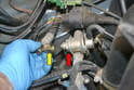 Use a 22mm wrench to support the regulator housing (red arrow) and a 19mm wrench to break open and remove the fuel line fitting (yellow arrow).