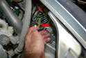 Reach in a separate the single electrical connection for the A/C compressor (red arrow) from behind the panel.