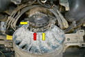 Tilt the alternator forward and remove the 13mm nut (red arrow) and the two 8mm nuts (yellow arrows).