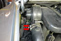 Use a Philips head screwdriver or 7mm socket and loosen the two upper clamps holding the tube to the blower (red arrows).