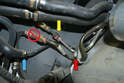 Follow the lines towards the forward section on the right side of the engine compartment where you find another plastic holder; use a 15mm wrench and remove the bolt holding it in place (red arrow).