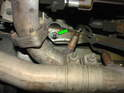 Shown here is the nut on the right (passenger) side of the engine (green arrow).