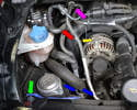 On the left side of the engine unclip the two coolant hoses and the brake booster pipe on the cross member and lay them off to the side (blue arrows).