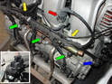 To remove the left side fuel distribution rail you will first need to remove the switch over valve (red arrow), push in the metal wire and pull the plug out, remove the plug from the camshaft positioning sensor (blue arrow and insert lower left).