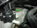 With the engine lowered, pull the coolant tank towards the engine (direction of green arrow).