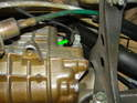 Remove the electrical connection going to the reverse light switch on the transmission towards the front of the car (green arrow).
