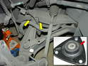 The yellow arrows in the photo show the bolt that needs to be loosened in order to gain enough clearance to lower the shock and clear the edge of the fender.
