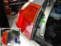 Open the engine lid and remove the 10mm bolt shown here to release the tail light housing from the body (green arrow).
