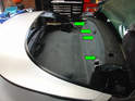 Pry out the four black plastic tabs holding the upper part of the carpeting to the roll bar bulkhead (green arrows).