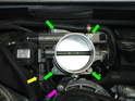 Remove the four 10mm bolts (green arrows) and also the 10mm nut (purple arrow) holding the throttle body to the engine.