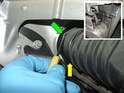Using pliers or a small flat blade screwdriver, remove the boost pipe-retaining clip (green arrow) from the intercooler outlet (yellow arrow).