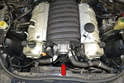 The coolant pump and thermostat are located in the front of the motor between the cylinder banks.
