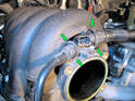 Squeeze the wide outer rings (green arrows) together on the breather hose connections at the top of the intake manifold and pull them out.