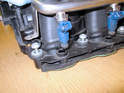 Once all the mounting screws are removed, carefully pull up on the fuel rail to separate the fuel injectors from the manifold as shown here.