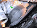 Release tension on the serpentine belt and pull the belt up and over the front of the pulley (see our article on serpentine belt replacement for more information).