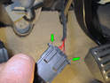 Squeeze the plastic tabs (green arrows) inward on the electrical connector and pull it out of the brake light switch.