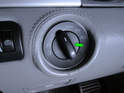 Press the center knob (green arrow) of the headlight switch inward and rotate it clockwise until it stops.