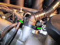 Press the two tabs (green arrows) on either side of the air hose connection going to the left side valve cover.