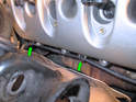Remove the lower wiring harness from the two metal clips on the lower side of the valve cover (green arrows).