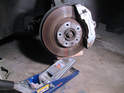 Place a floor jack with a block of wood under the front control arm behind the brake rotor.