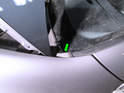Remove the small trim piece (green arrow) from either end of the windshield.