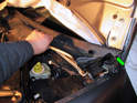 Carefully pull the wiper motor cover up where it meets the windshield.