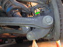 Begin by removing the sway bar end link (green arrow) This is bolted to the sway bar at the top and the shock absorber mount at the bottom.