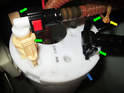 Left side of car: Squeeze the tabs (green arrows) on the fuel line connectors at the top of the fuel pump and pull the connectors up and out.
