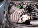 Both sides of car: Tilt the filter housing (green arrow) towards the engine to remove it from the car.